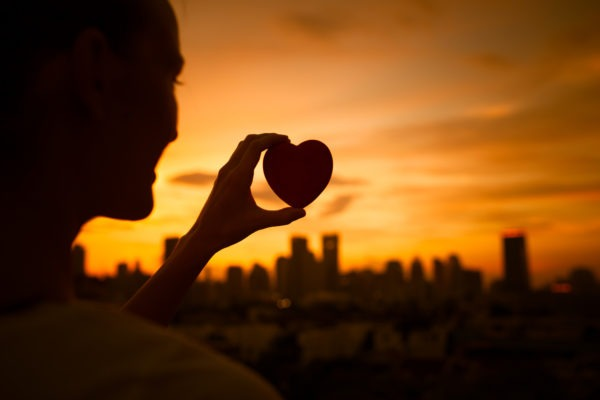 image of Love and happiness concept. Silhouette of woman holding up heart in the city.