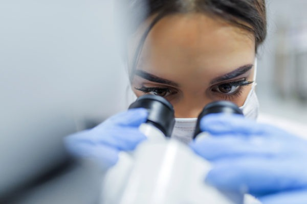 image of Close up of Young scientist looking through a microscope in a laboratory